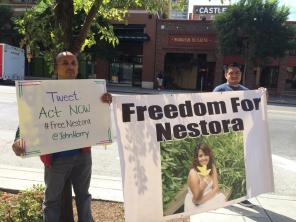 Nestora's husband holding a sign asking supporters to tweet: Act NOW to #FreeNestora @JohnKerry